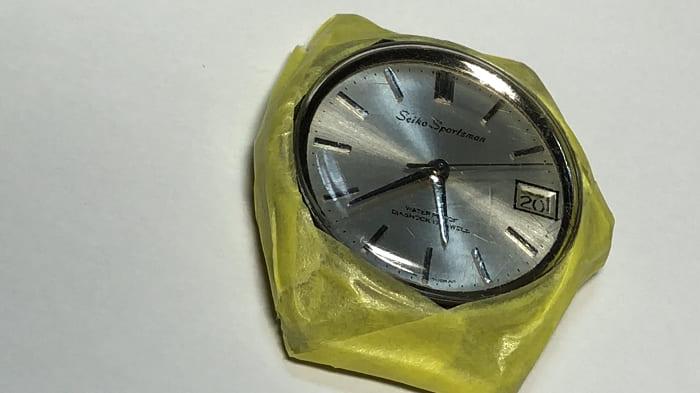 マスキングテープで時計ケースを保護している